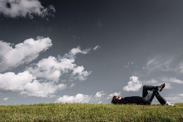 寝ころぶ男性と空の画像